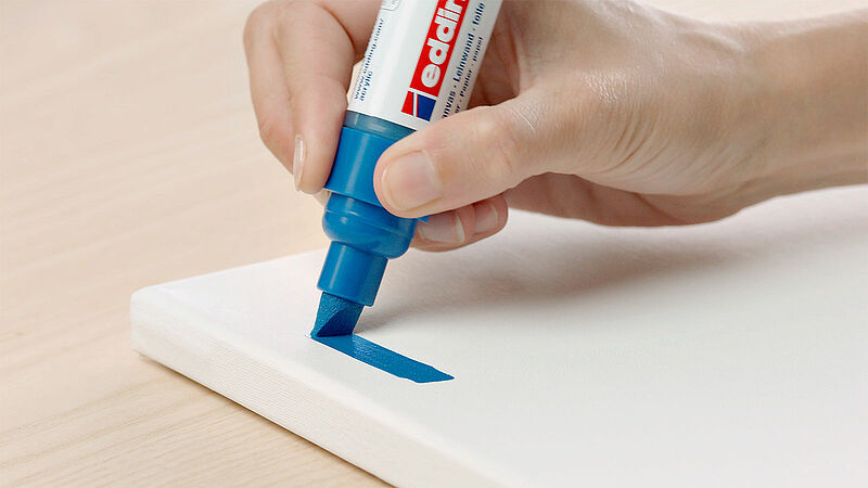 A blue edding acrylic marker being used on a white canvas