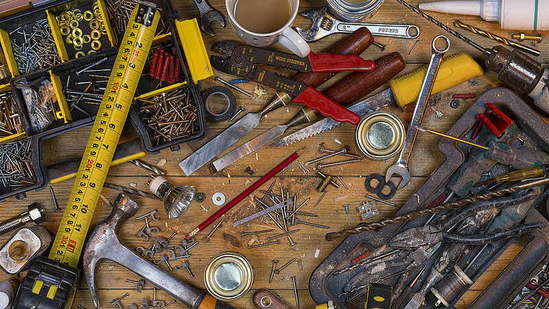 Untidy workbench full of dusty old tools and screws