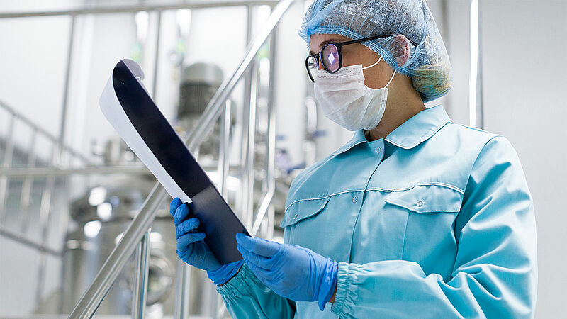 Woman looking at a clipboard in sterile factory production