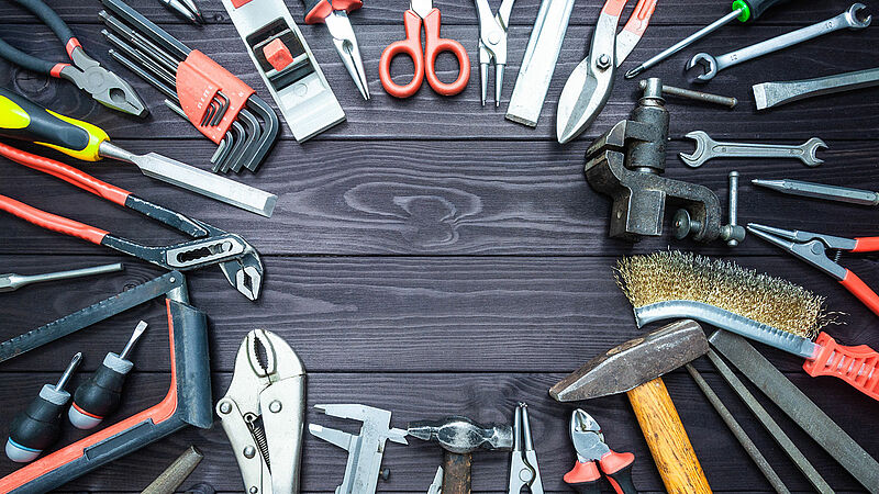 Background with various tools on wooden workbench