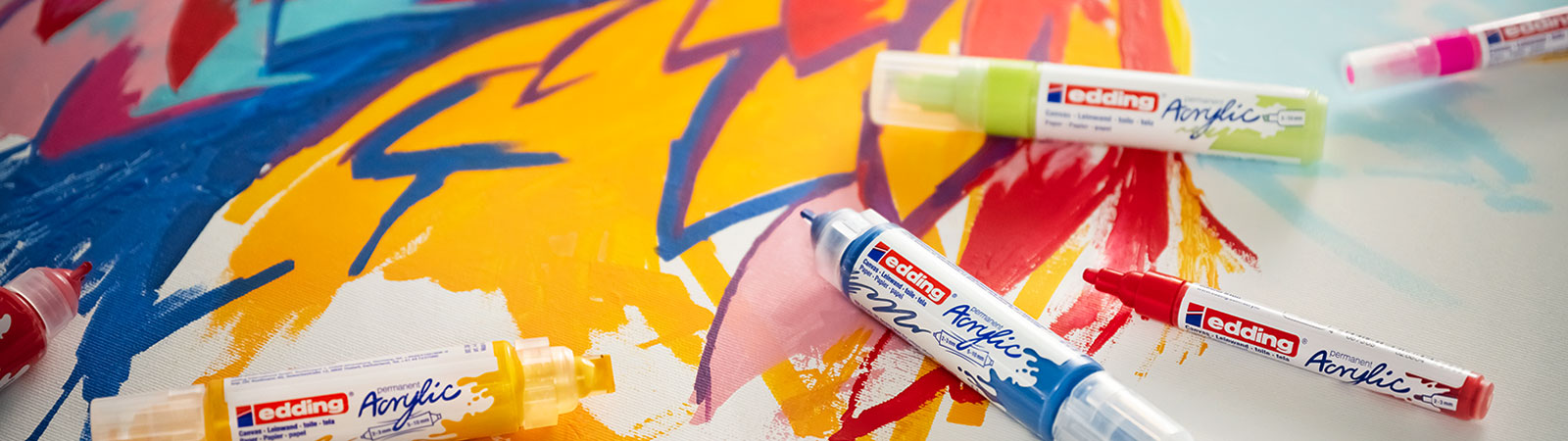 edding Acrylic markers scattered across a colourfully painted canvas