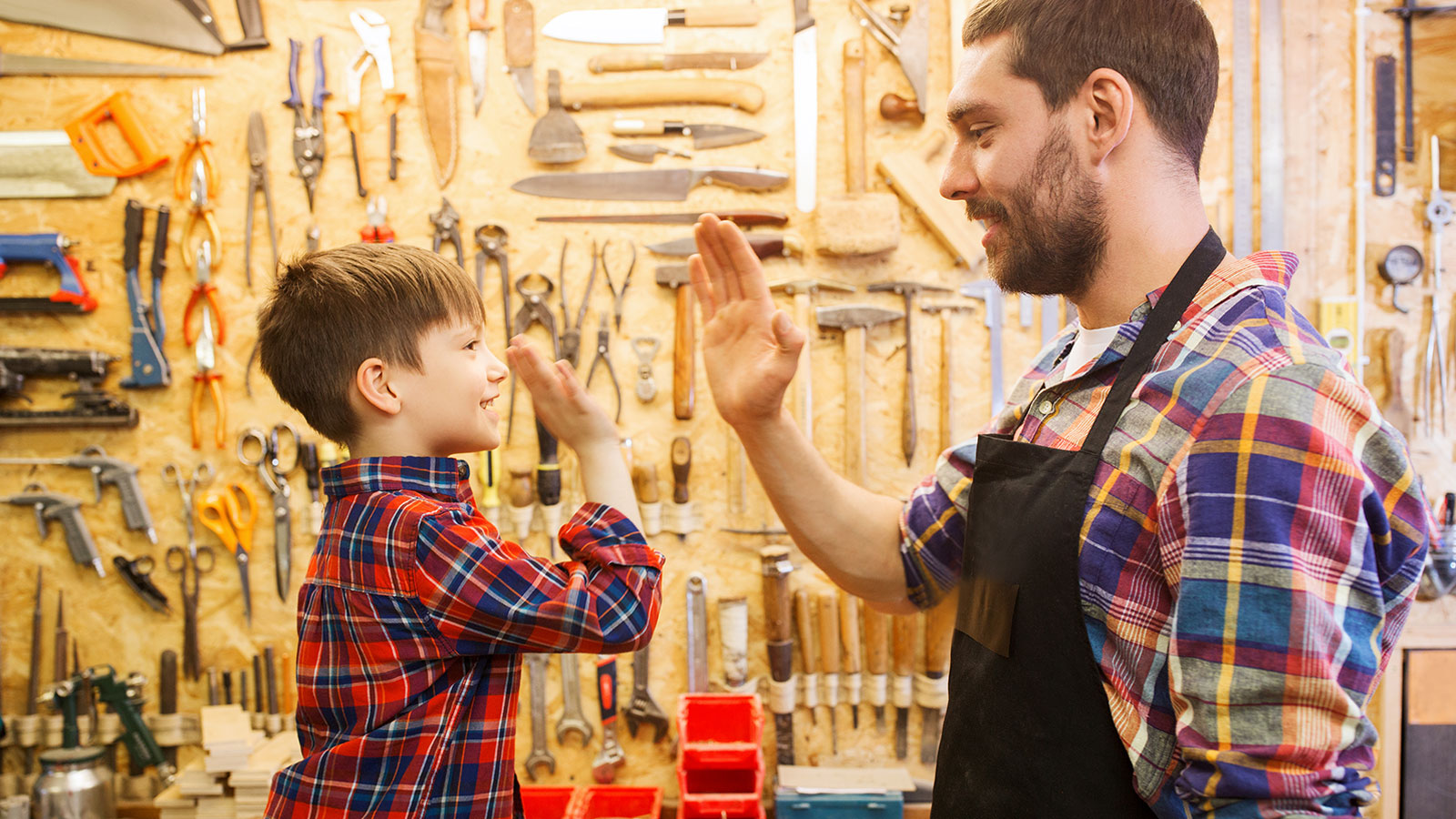 Carpenter father and son making high five at workshop