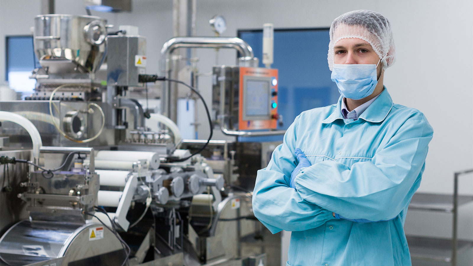 Factory worker in blue lab uniform and facemask