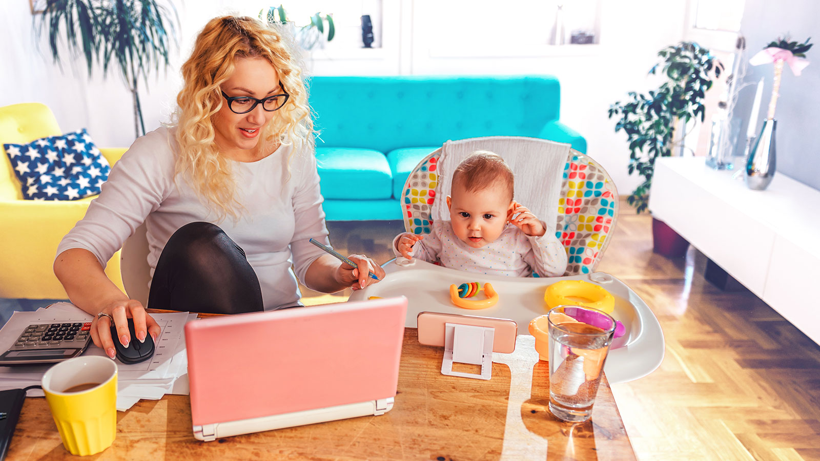 Mother working from home with a laptop in front of her and her toddler in highchair next to her