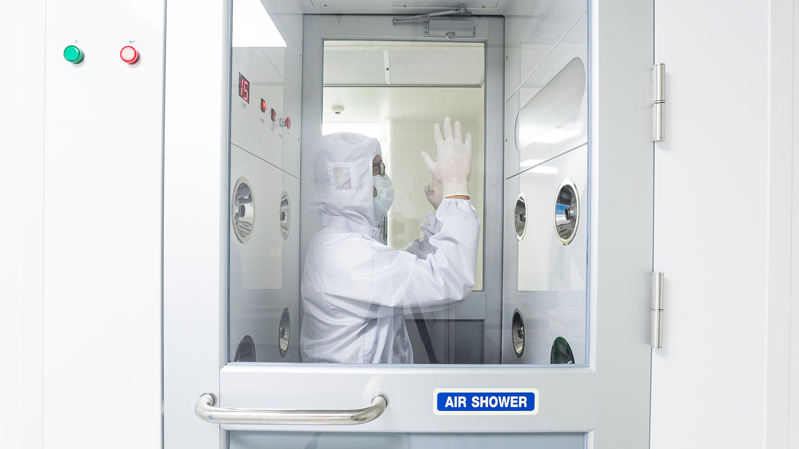 Man in sterile coverall gown using air shower to remove particle contamination